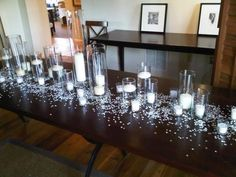 THIS IS EXACTLY WHAT I WANT OUR KING TABLE TO LOOK LIKE - LOTS OF Candles in Glass Cylinders - add two tall vases at either end of simple gladiolus and call it a day!