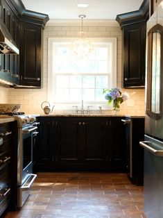 very striking kitchen for a small space; black cabinets, white subway tile, and cool chandelier