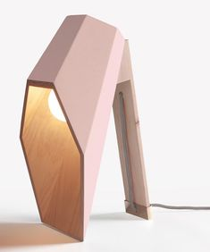 Lamp designed with a hexagonal wooden shade that extends over its light bulb like a hood.
