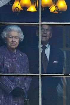 Britain's Queen Elizabeth II (L) looks out of a window from inside Kensington Palace with her husband, Prince Philip, Duke of Edinburgh (R) in London, Britain, 15 March 2012. The Queen toured the palace following a major refurbishment and it will open to the public