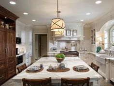 Two light fixtures hang above a large white kitchen island. A combination of wood and white cabinetry complements the white marble countertop on the kitchen island, creating an elegant contemporary look.
