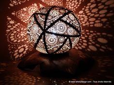 Lampe Elina Calebasse du Sénégal Diamètres : 18,3 cm et 15,8 cm Perforations : 1.2 mm à 6 mm Teintes : Chêne clair-Merisier Vernis :   Tek de Java - Acajou  - incolore  Socle en racine de Tek Dimension : 20 cm x 31 cm Teintes : Merisier Cire : Chêne foncé Eclairage : LED 20W Juillet 2017