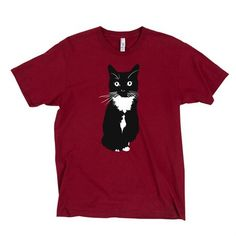 Time spent with cats is never wasted.   Sigmund Freud   This cranberry red t-shirt features an illustration of dapper tuxedo cat Fritz, one of our three shop cats. It was designed and screen printed by hand at Old Town Press on Staten Island in New York City, using eco-friendly waterbased inks on 100% cotton shirts.    Brand: American Apparel   Colors: Cranberry Red   Garment Details: 4.3 oz. 100% ringspun cotton, unisex   Ink: Eco-friendly waterbased ink   This shirt is part of our…