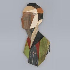 Strook hängt geometrische Holzköpfe an Hauswänden auf