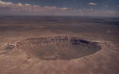 Barringer Meteor Crater. Near Winslow, AZ. About 1.2 km across and .2 km deep. An impact about 25,000 years ago. The meteor that caused it is estimated at 50 meters diameter which would have weighed about 300,000 tons. Photo by Brad Snowder.