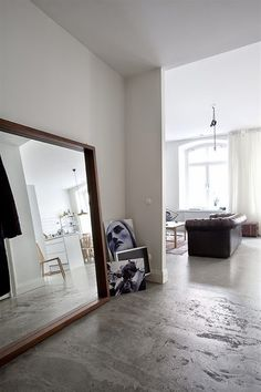 concrete floor + leaning mirrors & art