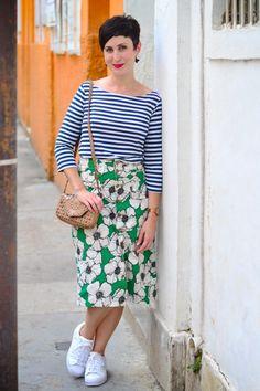 blusa de malha com mangas listrada azul e branca, saia mídi reta de brim com estampa verde com flores brancas e pretas e botões frontais, tênis adidas branco