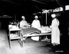 African-American US Army nurses 2nd Lt Prudence Burns, 2nd Lt Elcena Townscent, and a 3rd nurse treating Sgt Lawrence McKreever at 268th Station Hospital, Base A, Milne Bay, New Guinea, 22 Jun 1944