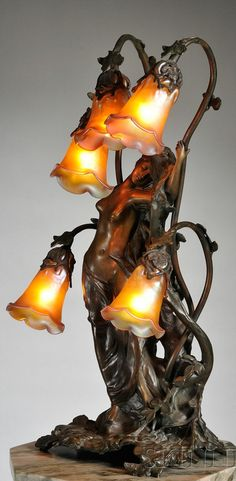 Gustav Gurschner Art Nouveau Table Lamp Bronze and Glass, Austria, female figure leaning against a tree trunk with five branches terminating in shades which are blown into the metalwork, marked Gurschner in the casting, ht. 24 1/8 in. | SOLD $4,150 Boston 2010