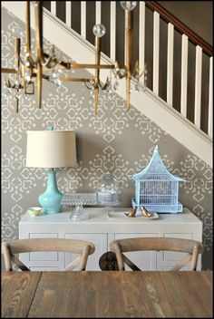 Turquoise lamp and birdcage add life to this console in a neutral gray room