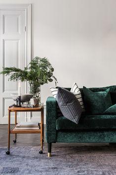 Elegant Scandinavian interior | Dark green velvet sofa | retro style bar cart with seasonal greenery on it | striped cushion covers | simple holiday decor | IKEA Karlstad sofa with a Bemz cover in Viridian Zaragoza velvet