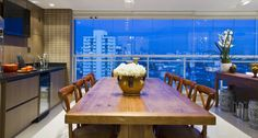 Neste projeto da arquiteta Camila Klein, a varanda ganhou uma grande mesa e uma churrasqueira para que a família pudesse receber os amigos e familiares nos finais de semana Foto: Bruno Netto / Divulgação