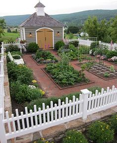 Dream garden-brick pathways separate individual garden plots, white picket fence surrounding all, even includes a potting shed that looks like a rural church, pray for good things to grow, and a bountiful harvest?