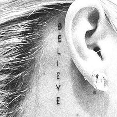 "Little tattoo behind the ear saying ""Believe""."