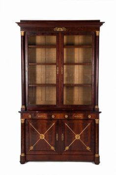 An Empire Two-body Display Cabinet. Mahogany veneer. The top part having two glass doors; The lower part with two doors concealing two drawers; Finely chiselled gilt bronze applications. They complement the front free-standing columns having gilt bronze capitals; France, 19th century - Dim: 256x150x62cm European Furniture, Antique Furniture, Furniture Board, Furniture Design, Classic Bar, Empire Style, Neoclassical, Glass Doors, Furniture Inspiration