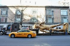 "Conceptual artist Serkan Ozkaya's double-size, golden replica of Michelangelo's ""David,"" titled ""David (inspired by Michelangelo),"" arrives Tuesday on a lowboy trailer at the Storefront for Art and Architecture in New York City. The sculpture spent the day the traveling throughout the city on the trailer. Photo by Slaven Vlasic/Getty Images."