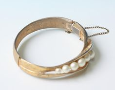 Vintage gold tone metal hinged bangle bracelet is decorated with an asymmetrical row of faux pearls. Bracelet is in very good vintage condition with no obvious signs of wear. To see more photos or purchase here's the link https://ww...