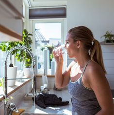 Side view of woman in sports clothing drinking water at kitchen - Womens Health Magazine  IMAGES, GIF, ANIMATED GIF, WALLPAPER, STICKER FOR WHATSAPP & FACEBOOK