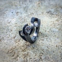 The Meghan Black Titanium engagement ring is a definite show-stopper! This one-of-a-kind creation features a triple tension setting that makes your Diamonds or gemstones appear to float in a flowing wave.
