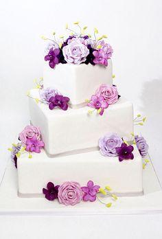Torta de boda de tres niveles cuadrada, decorada con flores violetas. #BodasVioletas
