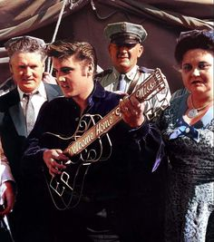 Facing the press before his afternoon show in Tupelo in september 26th 1956 here with Vernon and Gladys , receiving the key of Tupelo in a guitar shape.