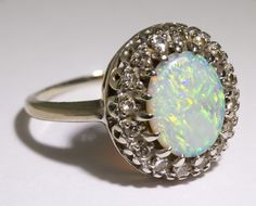 Lot 277: 14k White Gold, Opal and Diamond Ring; Having an oval cut cabochon opal surrounded by sixteen round cut diamonds