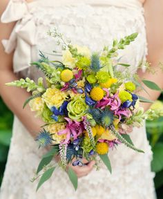 A fabulous loose and airy bouquet created of seeded euc, pink veronica, blue thistle, yellow snapdragons, blue delphinium, yellow billy balls, yellow carnations, green button mums, green cabbage roses, and hot pink nerine lily.