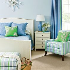 Much like in the living room, the daughter's serene bedroom took its inspiration and palette from a bright green accent pillow. With an eye to toning down the vivid neon hue, Howard introduced calming shades of white and a mix of lighter and deeper blues on the walls, furniture, and accessories to create balance.  Get the Look: The walls are painted Misty Blue by Benjamin Moore.