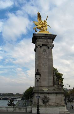 One of the four gilt bronze sculptures which overlook the Pont Alexandre III and the Seine River, Paris. Each sculpture sits atop a 17 metre column. This bridge is the most ornate bridge in Paris  and it leads to the Grande Palais on the right bank.