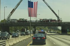 Central Pierce and Joint Base Lewis-McChord firefighters salute the procession of Capt. Douglas D. Ferguson's remains May 1, 2014, on an overpass in Tacoma, Wash. Ferguson, a Tacoma native, was killed while on a reconnaissance mission over Laos when his aircraft was shot down Dec. 30, 1969. (U.S. Air Force photo/Tech. Sgt. Sean Tobin)