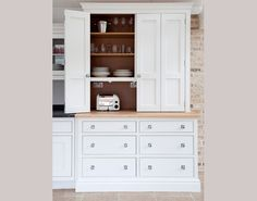 Bespoke storage solutions from Martin Moore & Company... shown here: a clever concertina door that folds back to reveal space to store crockery and appliances - www.martinmoore.com