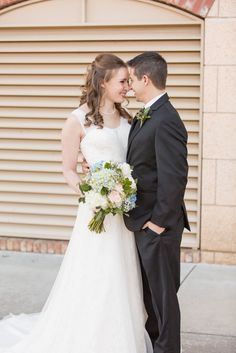 David's Bridal bride Michelle in an A-line tank wedding gown with lace detail and crystal belt by Oleg Cassini.