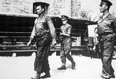 A mass murderer under arrest. Joseph Kramer, commandant of Bergen-Belsen concentration camp, wearing ankle shackles as he is put under guard by British military police.