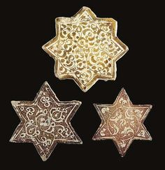 Description: THREE KASHAN LUSTRE STAR TILES CENTRAL PERSIA, 13TH AND 14TH CENTURIES Comprising two six-pointed examples, each decorated with scrolling arabesques reserved against a deep lustre ground filled with fine scrolls, together with a larger eight-pointed star tile with similar scrolling designs in lustre on a white ground, slight chips, smallest with one restored corner 6in. (15cm.), 5½in. (14cm.) and 4½in. (11.5cm.) wide (3)