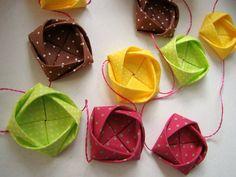 cordão de origamis de camélias feitos de origami em  tecido. possui 1,70 m de comprimento, contém 12 camélias e vem numa caixinha fofa de origami . são quatro cores são lindas! marrom, verde, pink e amarelo, todos com poas brancos. R$ 41,80