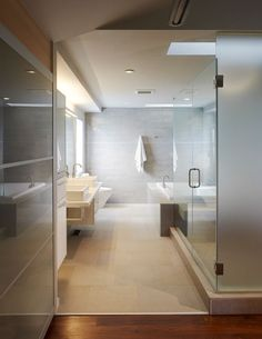 Modern bathroom design with large tiles, glass shower, and inviting bath tub.