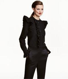 Black. Ruffled blouse in woven cotton fabric. Small stand-up collar, buttons at front, and narrow cuffs with buttons and ruffle.