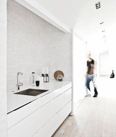 WHITE Kitchen Interior ::   Painted white brick wall.   Seamless white benchtop.    Gentle white wash oak floor boards.  Corian Kitchen