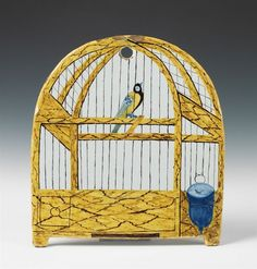 A Delft faience plaque with a grand feu depiction of a trompe l'oeil birdcage. Minor wear to the margins. H 28, W 25.5 cm. Late 18th / early 19th C.
