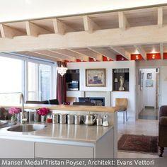 Die Dachbalken werden mit Wandleuchten und rot bemalten Flächen in Szene gesetzt. Verbuden mit Zimmerpflanzen ergibt sich eine sommerlich-natürliche  …