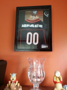 Shadow box  with dog jersey,  photo and team sticker all inside.  Nice keepsake for your furry baby.