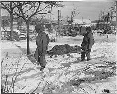 Soldiers carrying the body of a victim of the Malmedy Massacre during the Battle of the Bulge.