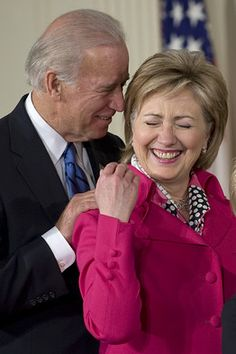 Hillary Clinton wears a hot pink pantsuit designed and custom made by Susanna Beverly Hills while having a laugh with Joe Biden. Vice President Joe Biden and outgoing Secretary of State Hillary Rodham Clinton are arguably the top two potential candidates for the '16 Democratic nomination in the 2016 presidential race http://blogs.rep-am.com/worth_reading/2013/01/30/hillary-and-joe-down-the-road/ See more of Susanna Beverly Hills Haute couture collection at www.susannabh.com