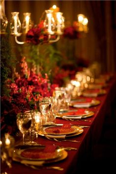 Beautiful  red gold chargers, round menu cards, lovely centerpiece and I really like the chandelier low over that large table!