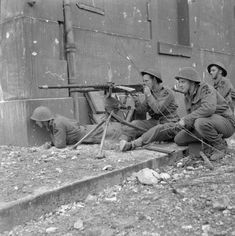 Troops of 1 Kings Own Scottish Borderers (KOSB), 9th Brigade, 3rd Infantry Division, firing a captured Hotchkiss machine gun during street fighting in Caen, 10 July 1944.  (rw)