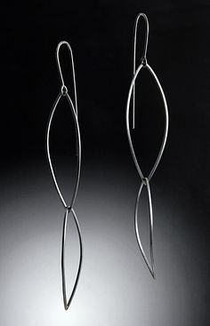 Curved Shields Earring by Grace Stokes. Long and feather light, these double shield earrings just kiss your shoulders, making the most of minimal contemporary design. Oxidized sterling silver. Sterling silver ear wires.