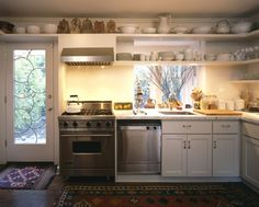 white and bright kitchen with open shelving and lots of white pottery & dishes, oriental rug
