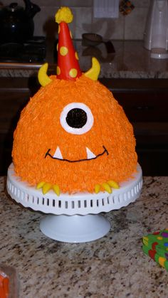 Monster cake (I used the Wilton Classic Wonder 3D Cake Mold on top of an 8 inch round. Ice cream cone covered in fondant for the hat and the eye is made out of wilton sugar sheets.