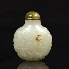 CHINE - XXe siècle  Flacon tabatière de forme arrondie en néphrite légèrement rouille à décor sculpté en léger relief de branches de citrons digités et pêches de longévité mouvementées.  Bouchon en jadéite cerclé de métal doré.