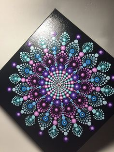 Hand painted with acrylic in Pink, Teal, Blue, and Violet. Sprayed with a high gloss sealer to protect the colors. Canvas size is 8 X 8.